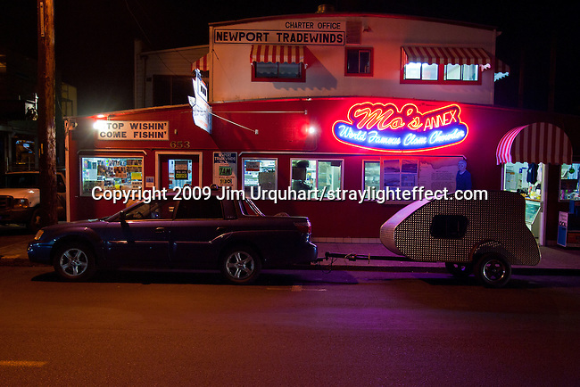 A Subaru Baja with a teardrop camping trailer is parked at night in front of Mo's, which is world famous for it's clam chowder, and the offices of Newport Tradewinds at the Harbor of Newport on the coast of Newport, Oregon off Pacific Coast Highway 101. Jim Urquhart/straylighteffect.com 7/23/09