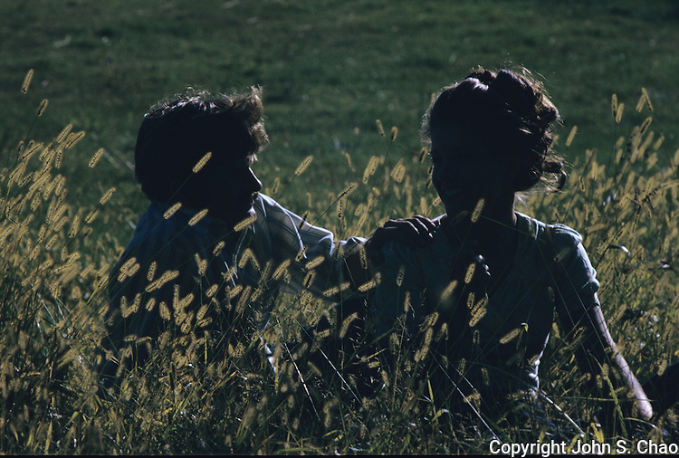 Silhouettes of a young couple sitting together in tall grass, backlit by sunlight. Taken on Kodak Ektachrome in 35mm format.