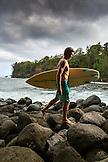 USA, Hawaii, The Big Island, portrait of a surfer on a rocky shoreline at the Hakalau River mouth, North of Hilo
