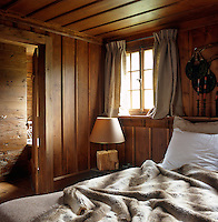 This small rustic bedroom has an ensuite bathroom and the bed a faux fur cover