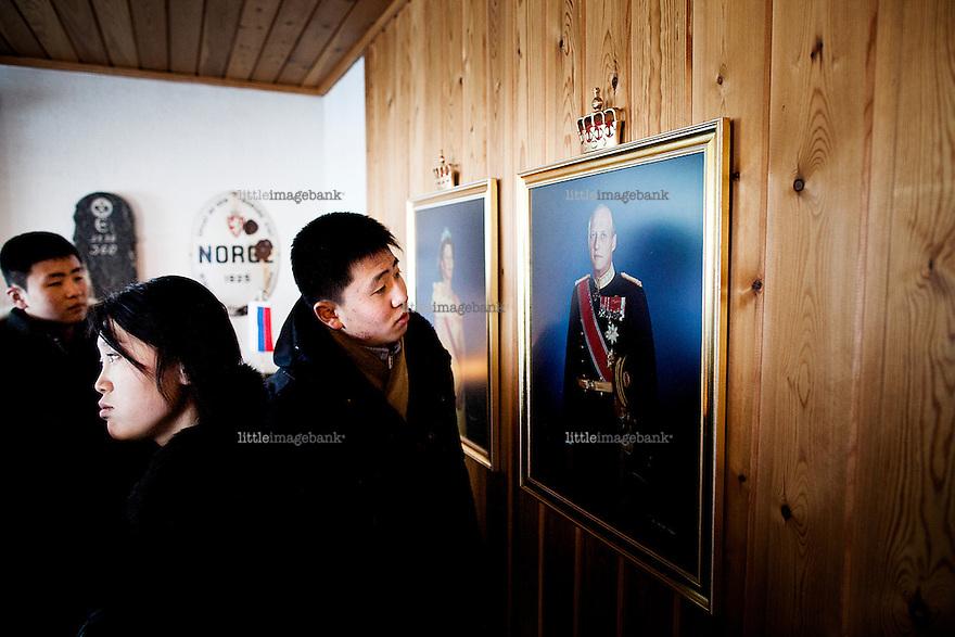 """Kirkenes, Norge, 08.02.2012. Fra venstre: Kim Chon Ryong (16), Han Jin Song (16) og Kim Ju Yong (15). De unge musikerne er på besøk på Storskog grenseovergang. Kim Ju Yong benytter anledningen til å studere den norske kongefamilien. Den 1. februar 2012 lastet kunstner Morten Traavik opp en videosnutt på You Tube av Nord-Koreanske ungdommer som spiller A-Ha hiten """"Take on Me"""" på trekkspill. En uke etter ha over en million mennesker sett videoen. En delegasjon Nord-Koreanere er i Kirkenes i forbindelse med festivalen """"Barents Spetakel"""". Foto: Christopher Olssøn"""