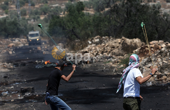 Palestinian protesters use a slingshot to hurl stones towards Israeli security forces during clashes following a weekly demonstration against the expropriation of Palestinian land by Israel in the village of Kfar Qaddum, near Nablus, in the occupied West Bank on June 30, 2017. Photo by Ayman Ameen