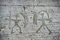 Prehistoric Petroglyph, rock carving, of two warriors with shileds and a spear carved by the Camunni people in the iron age between 1000-1600 BC, Seradina I rock 12, Seradina-Bedolina Archaeological Park, Valle Comenica, Lombardy, Italy