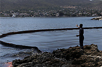 "Pictured: A floating barrier used to contain the oil spill that has reached the coast of Salamina, Greece<br /> Re: An oil spill off Salamina island's eastern coast is spreading and has become ""an environmental disaster"" according to local authorities in Greece.<br /> The spill was caused by the sinking of the Aghia Zoni II tanker, carrying 2,200 metric tons of fuel oil and 370 metric tons of marine gas oil on Saturday, southwest of the islet of Atalanti near Psytalleia. According to reports, the coastline stretching from Kinosoura to the Selinia community has ""turned black"" and authorities fear a new leak from the sunken ship.<br /> According to the island's mayor, Isidora Papathanasiou, the weather ""turned on Sunday afternoon and brought the oil spill to Salamina."""