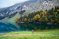 Trail running along the Seealpsee in the Alpstein group, a small mountain range in eastern Switzerland famous for it's unique landscape.