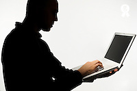 Silhouette of man using laptop (Licence this image exclusively with Getty: http://www.gettyimages.com/detail/sb10068346bf-001 )