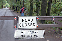 Road closure sign in Mount Rainier National Park due to 2006 flood and storm damage; no skiing or hiking allowed.