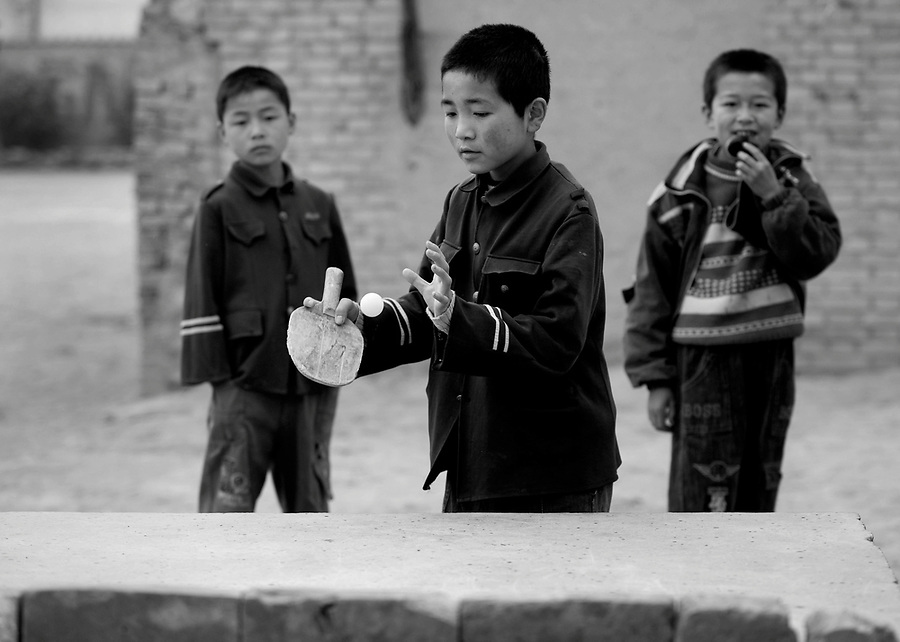 "A boy in a 'Mao"" jacket plays table tennis during a class break in Chuanhua county in China's poor Shanxi Province."