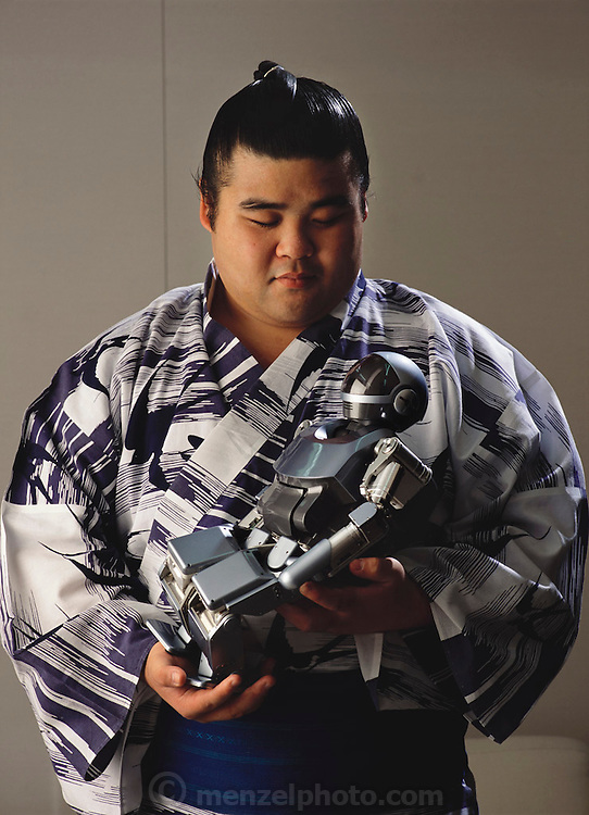 """The Sony humanoid robot prototype SDR-3X is held by professional Sumo wrestler Tamarashi (""""Bullet-storm""""). Sony Corporation announced the development of this small bipedal walking robot in November of 2000. By synchronizing the movements of 24 joints on its body, Sony says, the robot can perform basic movements such as walking and changing direction, rising from a seated position, balancing on one leg, kicking a ball, and dancing. Tokyo, Japan."""