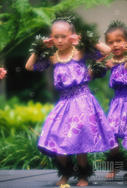 A keiki hula dancer from Halau Hula O Hokulani performing their Lei Day program at the Hilton Hawaiian Village