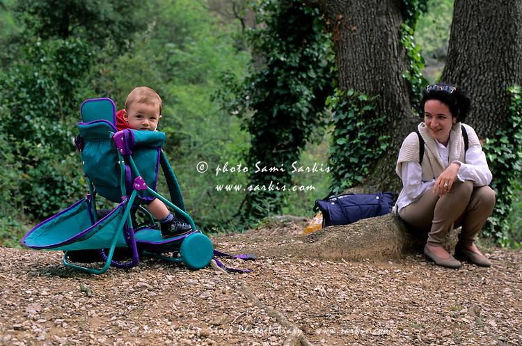 Mother out walking in a forest with her child in a baby backpack carrier.