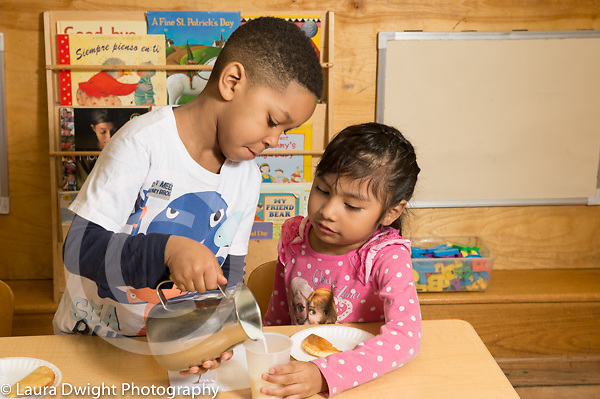 Education Preschool 4 year olds meal time boy pouring milk for classmate