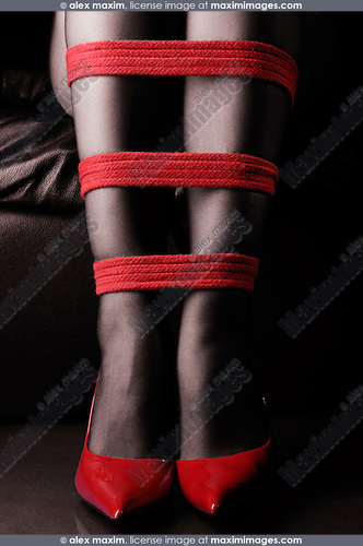 Woman in red shoes with her legs tied with bright red rope