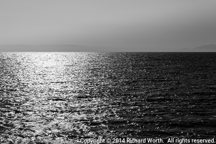 Shining, rippling water in black and white with faint mountain outline on the horizon.  Shining sun reflection on left with copy space on right and top.