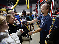 "NWA Democrat-Gazette/ANDY SHUPE<br /> Levi Crandell (right) with the Fayetteville Fire Department hands a firefighting ""Denver"" tool for students to hold Wednesday, Nov. 6, 2019, while describing firefighting equipment for a group of student fire marshals from Fayetteville Public Schools at the department's central fire station. Schools in the district appoint student fire marshals who assist staff and students during fire drills and emergency situations by guiding people to exits and ensuring that doors are closed at their schools."