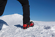 Appalachian Trail - Hiker wearing crampons on the summit of Mount Monroe with Mount Washington in the background in the White Mountains, New Hampshire during the winter months.
