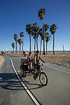 Pedicab cyclist and rider on the bike path in Santa Monica, CA