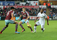 Pictured: Wayne Routledge of Swansea (R) finds it hard to get past James Tomkins (L) and Mark Noble (C) of West Ham Saturday 10 January 2015<br />