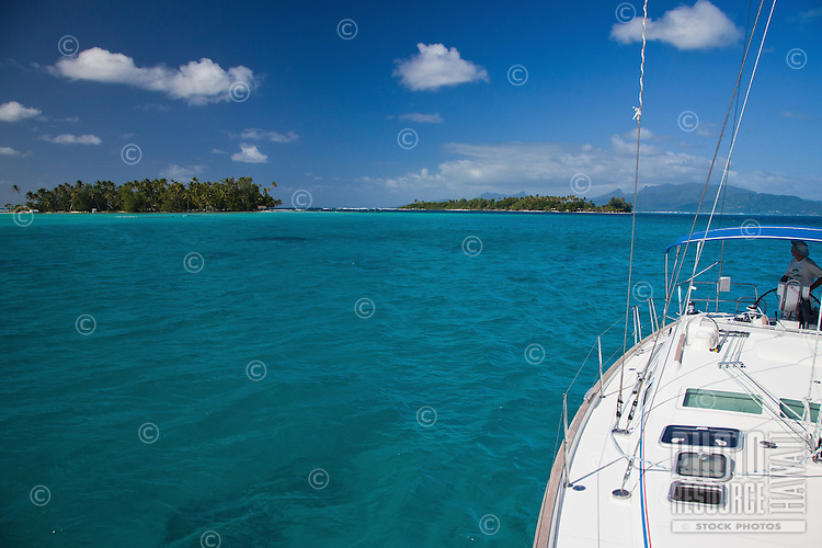 Man steering yacht in lagoon