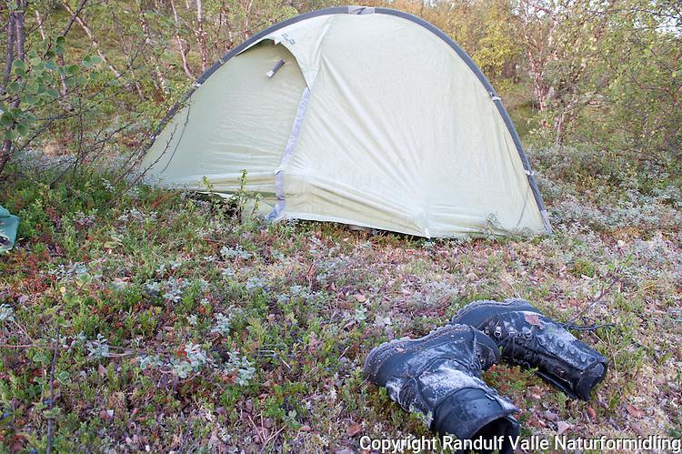 Frosne sko utenfor telt en tidlig morgen. ---- Frozen boots outside tent.