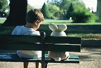 Boy (7-9) sitting on park bench with teddy bear, rear view (Licence this image exclusively with Getty: http://www.gettyimages.com/detail/200336682-001 )
