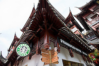 Starbucks coffee shop, American influence, alongside Chinese street signs in Yu Garden Bazaar Market, Shanghai, China