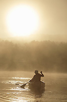 Hortonia, VT, USA - August 20, 2009: Girl paddling a canoe on a misty lake as the sun rises from behind the tree covered hills