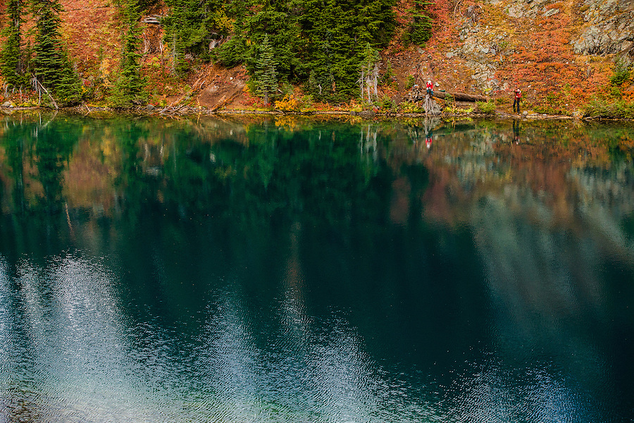 An woman sits and eats a snack while her male companion is engaged in fly fishing in Blue Lake in Washington's North Cascade Mountains.