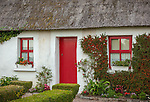 County Galway, Ireland: Thatched roof cottage with red doors and windows.