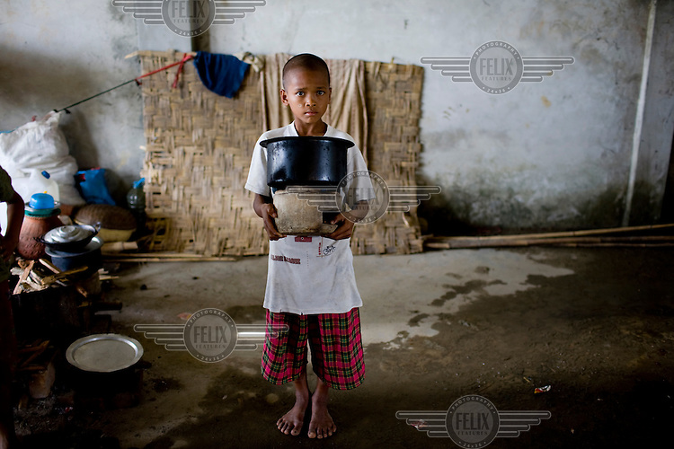 "When Cyclone Nargis hit the Irrawaddy Delta on 02/05/2008, all 13 year old Si Thu Aung could carry was a fire stove and pot. ""I wanted my toy, but my mother insisted on these. She asked me to take the pots and run as fast as I could."" Si Thu Aung lives with his mother alongside other refugees from the 7th ward, Hlaingthaya township in Rangoon (Yangon), in the Shwe Than Lwin shopping complex, which is under construction and has acted as a small refugee centre."