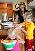 Heather Jacobs helps her son, Keenan, 7, with his homework while daughter Ella, 3, enjoys a bowl of popcorn in the kitchen of their Polk City home.  Heather lost her husband, Eric, in a plane crash in 2006 when she was eight months pregnant with Ella and has since been raising her five young children on her own.