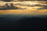 Silhouette of mountains at sunset from the along the Jewell Trail in Thompson and Meserve's Purchase in the New Hampshire White Mountains on cloudy summer day. The Jewell Trail is named for Sergeant Winfield S. Jewell. He was an Army Signal Corps observer on Mount Washington from 1878-1880. And on April 12, 1884, while on the Greely expedition to the Arctic, Jewell died of starvation. Out of the 25 men on the three year Greeley expedition (1881–1884), only six survived.