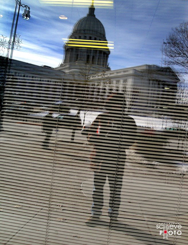 Wisconsin State Capitol reflected in office window.