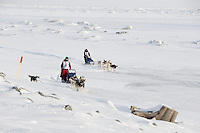 Lisbet Norris on the trail just outside Nome on the Bering Sea with Marcelle Fressineau behind her on Saturday March 15 during the 2014 Iditarod Sled Dog Race.<br /> <br /> PHOTO (c) BY JEFF SCHULTZ/IditarodPhotos.com -- REPRODUCTION PROHIBITED WITHOUT PERMISSION