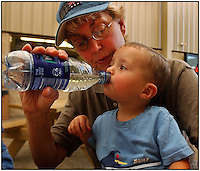 A grandmother gives a drink of water to her grandson. Model released image can be used to illustrate many purposes.