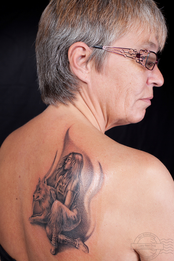 Danish woman with wolf and indian girl tattooed on her right shoulderblade.<br /> From the Kolding Tattoo Convention, Denmark