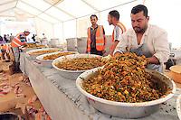 MOH04 RAS EL JEDIR (TÚNEZ) 6/5/2011.- Varios voluntarios preparan la comida para los refugiados del campo del Alto Comisionado de Naciones Unidas para los Refugiados (ACNUR) levantado en el paso fronterizo de Ras el Jedir (Túnez), que acoge a los desplazados de varias nacionalidades que han pasado de Libia a Túnez huyendo de la sangrienta rebelión contra el líder libio, Muamar Al Gadafi, hoy, viernes 06 de mayo de 2011. EFE/MOHAMED MESSARA..