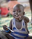 A boy gestures as he eats porridge in an emergency feeding program for malnourished children at the Loreto Girls School in Rumbek, South Sudan. The school, run by the Institute for the Blessed Virgin Mary--the Loreto Sisters--of Ireland, has opened its compound to hundreds of nearby villagers facing hunger because of ongoing conflict and climate change.