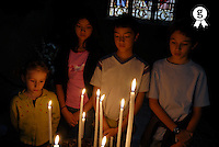 Children (6-13) praying by candles, close-up (Licence this image exclusively with Getty: http://www.gettyimages.com/detail/200482354-001 )
