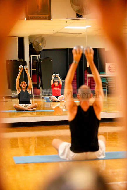 Pharmacy senior Ashley Stack, foreground, follows kinesiology senior Patrick Sims' exercise instructions during the yoga class held at the Johnson Center on Monday. Photo by Zach Brake | Staff