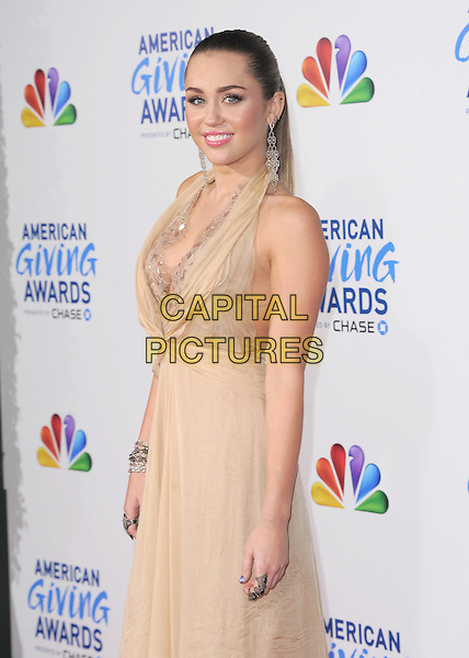 Miley Cyrus .attends The  American Giving Awards held at Dorothy Chandler Pavilion in Los Angeles, California, USA, .December 9th 2011..half length 3/4  hair up make-up beauty beige dress lace halterneck nude silver dangly earrings       side .CAP/RKE/DVS.©DVS/RockinExposures/Capital Pictures.