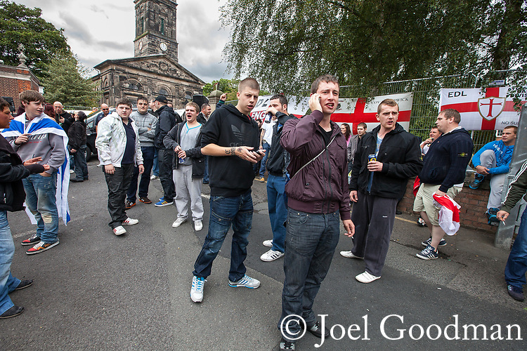 © Joel Goodman - 07973 332324 . 13/08/2011 . Shropshire , UK . Approximately 300 EDL supporters demonstrate against a paedophile ring in the small Telford town of Wellington . The group had planned to march, however the Home Secretary has imposed a ban on all marches in the area just days after riots have swept across England. A counter-demonstration has attracted about 300 people . Photo credit : Joel Goodman
