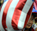 Jacki Federigan, 8, (Jacki) of Ellington, peaks through some red, white and blue balloons, prior to the step off of the kids parade  in Rockville, Tuesday, July 3, 2012, during Vernon's July 4tn celebration. (Jim Michaud/Journal Inquirer)