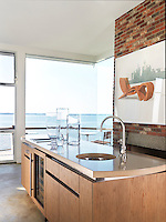 View over the kitchen island through a floor-to-ceiling picture window to the sea beyond