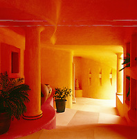The walls and pillars of the entrance hall are painted in inviting yellow, orange and pink