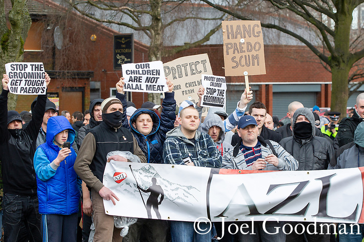 """© Joel Goodman - 07973 332324 . 03/03/2012 . Heywood , UK . Protesters hold an """" Anti Zionist League """" banner and placards reading """" Hang paedo scum """", """" Our children are not halal meat """" , """" Stop the grooming get touch on paedo's [sic] """" and """" Protect british children stop the grooming """" . The National Front hold a rally in protest against an alleged paedophile ring that had been operating in the area . There is currently (3rd March 2012) a case being tried at Liverpool Crown Court in relation to the allegations . Last Thursday (23rd February 2012) a protest organised in the town in relation to the same story resulted in Asian business being attacked by an angry mob . Photo credit : Joel Goodman"""
