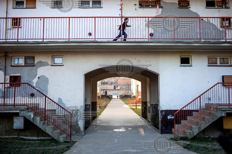 A child runs along a walk way in an apartmenbt block in the district of Stara Tehelna. This suburb is a segregated district populated by Roma who were moved en mass out of the city centre in 2001.