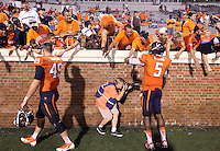 Photographer Ryan Jones crouches under Virginia players photographing the 19-16 celebratory win over Brigham Young in Charlottesville, Va. Photo/Andrew Shurtleff