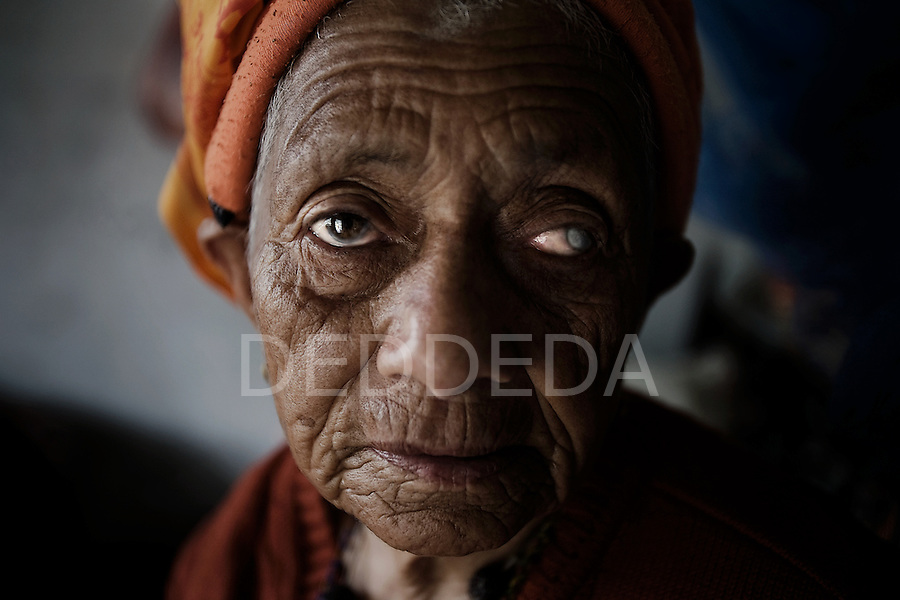 """An elderly woman looks into the camera at an """"Aged Shelter"""" in Pokhara, Nepal. The shelter is a place for seniors to live who have no other family members to look after them. The shelter has no running water, the cooking is done over a fire, there are no nurses or doctors, no heating, and no medication available for the residents."""