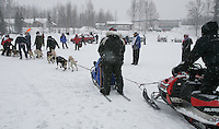 Saturday February 25, 2006 Willow, Alaska.   A snowmachine is used to slow and control Melissa Owens'  team as they head to the start line at the start day of the Junior Iditarod sled dog race.  Willow Lake.